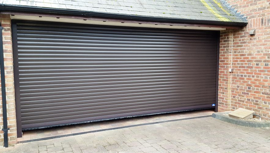 Darkly coloured foam filled security roller shutter in front of garage opening