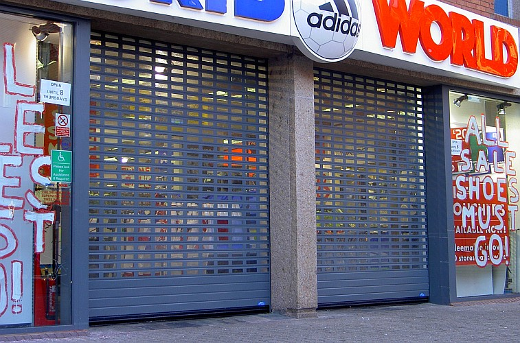 Pair of aluminium roller shutters over the entrance to a shop.