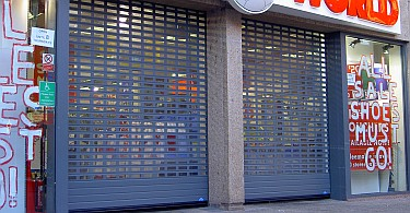 A pair of shopfront aluminium roller shutters with cutouts and polycarbonate infill.