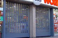 Polycarbonate infill panels on roller shutters with punch-outs.